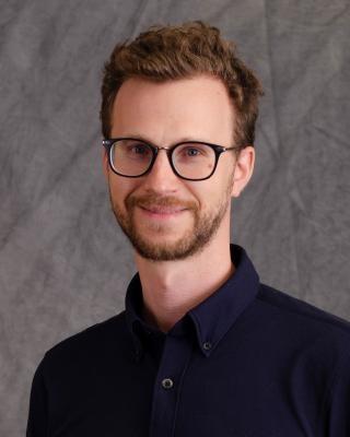 Seth Erickson headshot in black shirt and glasses