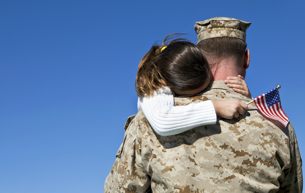 Military dad holding daughter