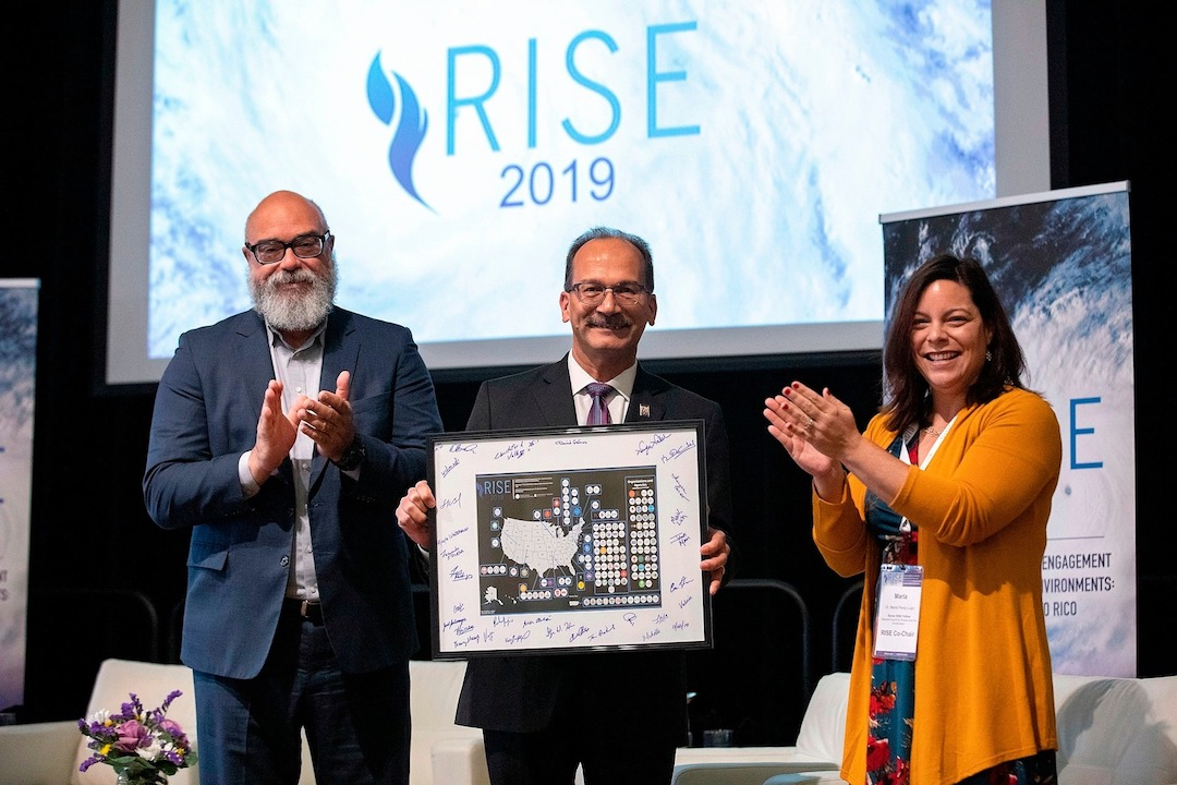 Cecilio Ortiz-Garcia, left, and Marla Perez-Lugo, right, present Havidán Rodríguez, president of the University at Albany, State University of New York, with a map depicting the reach of the RISE Network.