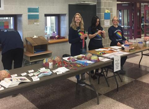 Photo of SLEIC team members standing at tables at Mount Nittany Middle School.