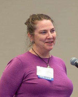 Photo of Claudia Brugman with her hair pulled back and wearing a purple blouse.
