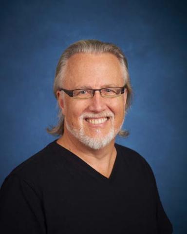 Headshot of David Baker with long gray hair, glasses, beard, and black shirt.