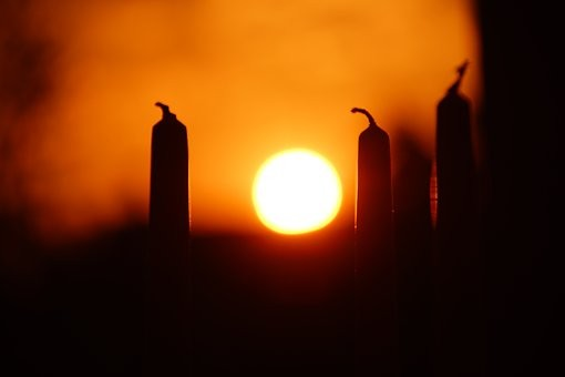 Unlit candles with sunset in background