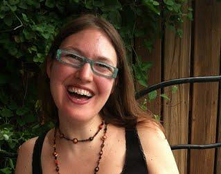 Headshot of Eleonora Rossi with long brown hair, glasses, and black top.