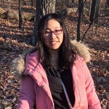 Headshot of Haoyun Zhang with black hair, glasses, black shirt, and pink coat.