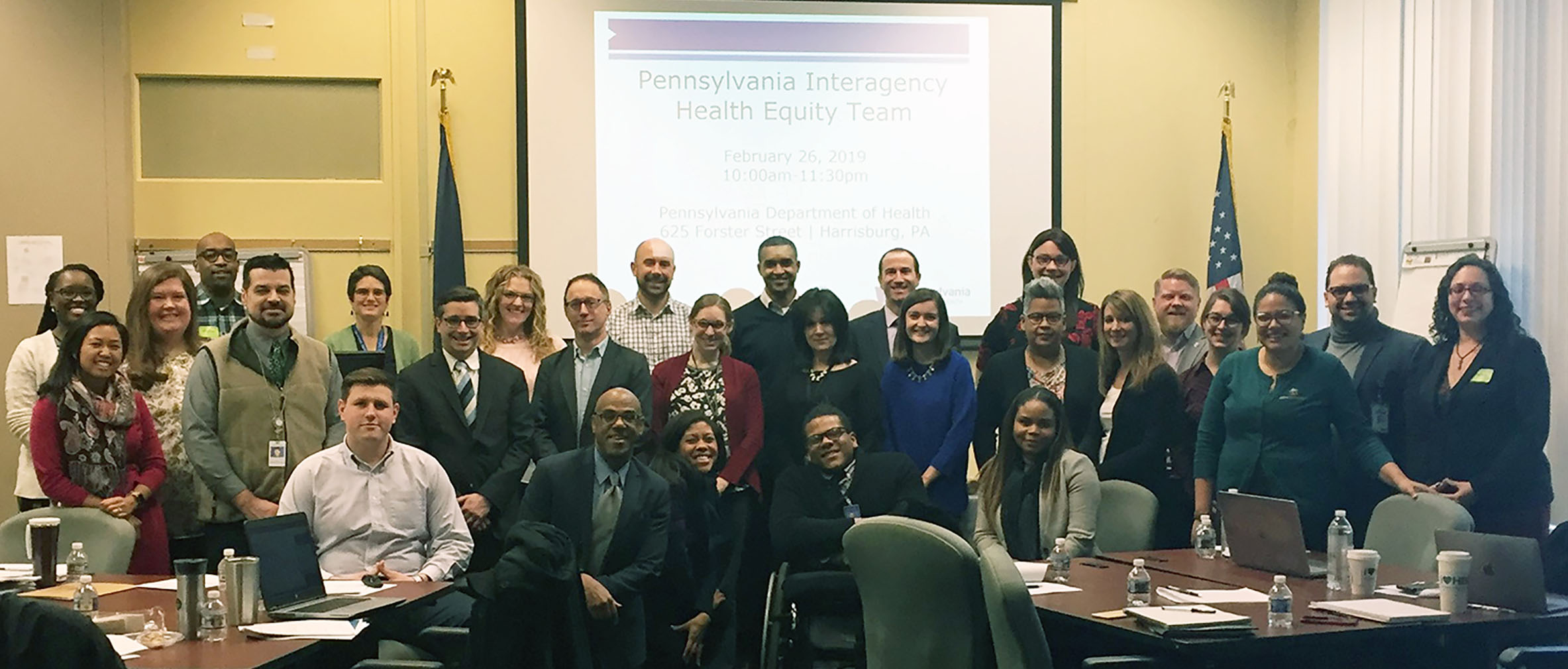 Photo of the large group of people on the Health Equity Team standing at the front of the room during a conference.