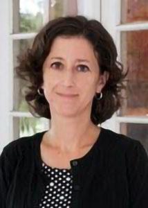 Jennifer Glick headshot with black meduim length hair, black cardigan and black and white blouse.