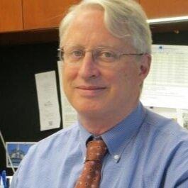 John Haaga headshot in blue shirt, orange tie