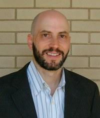 Headshot of John Iceland with beard, white shirt with thin stripes, and black jacket.