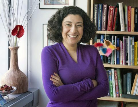 Headshot of Koraly Pérez-Edgar with black hair and purple blouse, standing next to a decorative vase and a bookshelf.