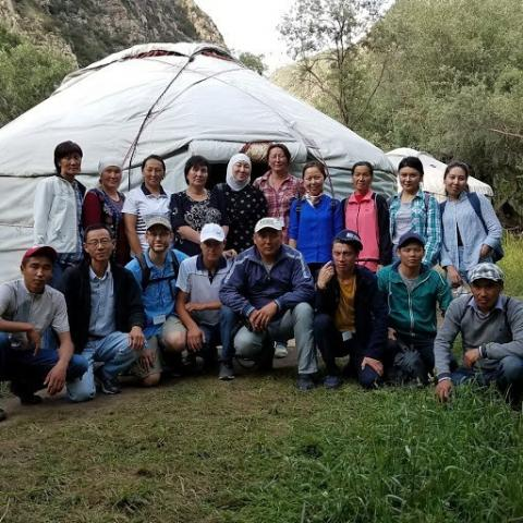 Photo of researchers, data collectors and translators in Alay Rayon, Osh standing in front of a tent. Oblast