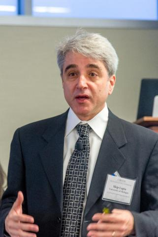 """Photo of Arthur """"Skip"""" Lupia with gray hair, white shirt, patterned tie, and dark gray jacket."""