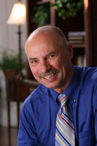 Headshot of Neil Sharkey with mustache, blue shirt, and multi-color striped tie.