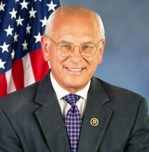 Headshot of Paul Tonko with white hair, glasses, white shirt, blue checkered tie, gray jacket, and the United States flag behind him.