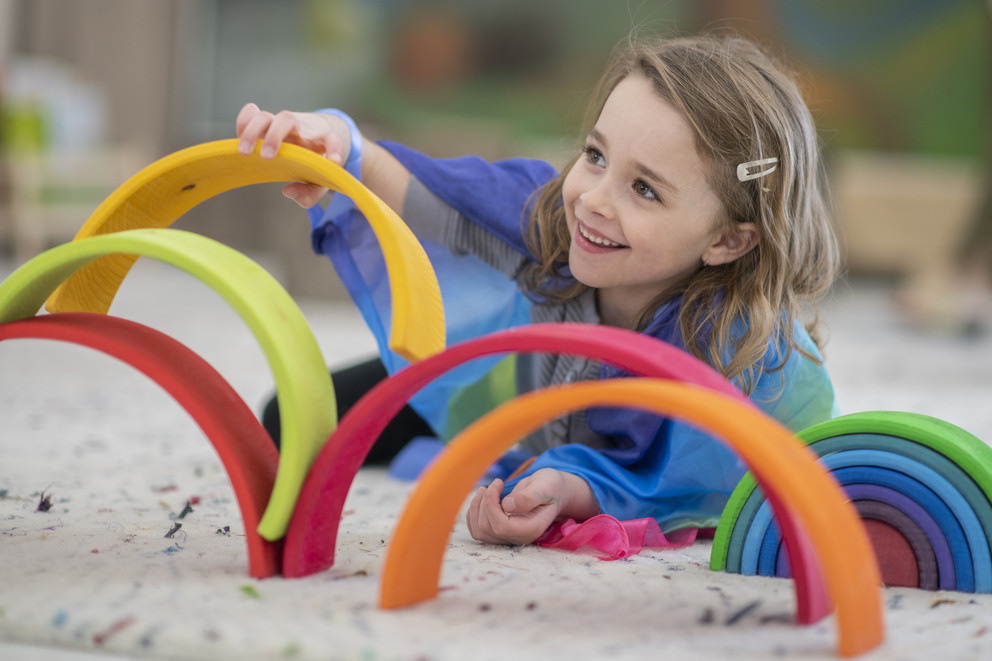Preschool girl playinig in sandbox with colored rings.