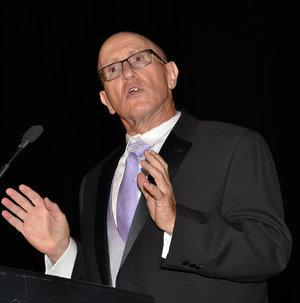 Photo of Ronald Wasserstein with glasses, purple tie, white shirt, gray vest, and black jacket.