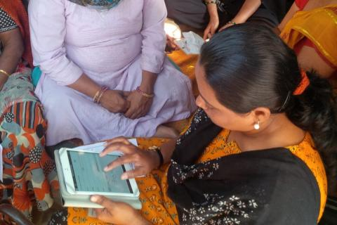 Hindu women sitting together with an iPad.