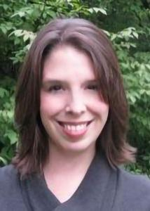 Sarah Damaske head shot in black shirt, medium-length brown hair.