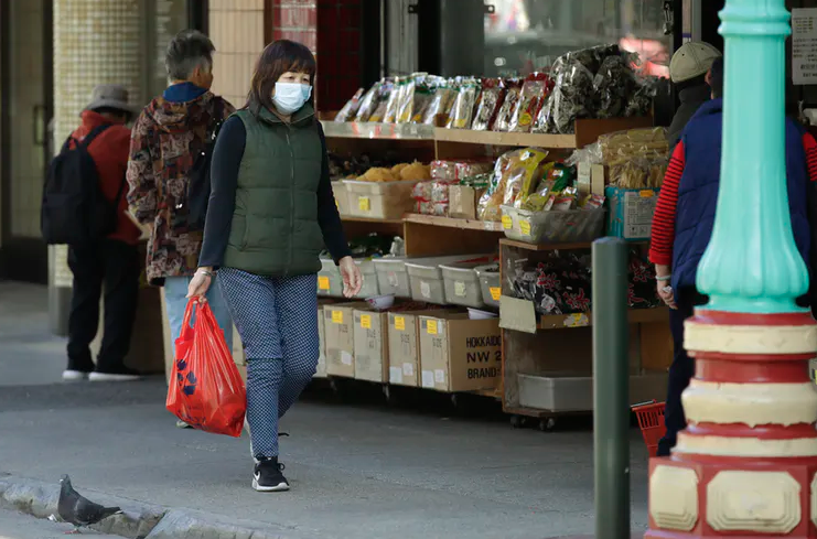 A masked shopper walks in the Chinatown district of San Francisco.