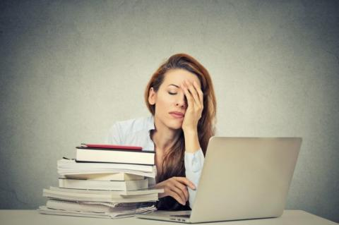 Photo of a sleepy woman in front of a laptop and a stack of books.