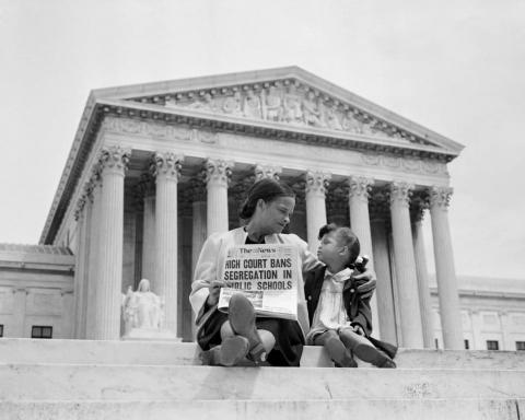 An African American mother and daughter sit on the steps of the US Supreme Court Building holding a newspaper announcing banned segregation.