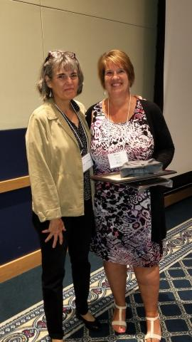 Photo of Sherry Yocum holding her award and standing next to Susan McHale.