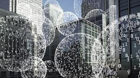 Spheres of 0s and 1s in front of a city landscape.