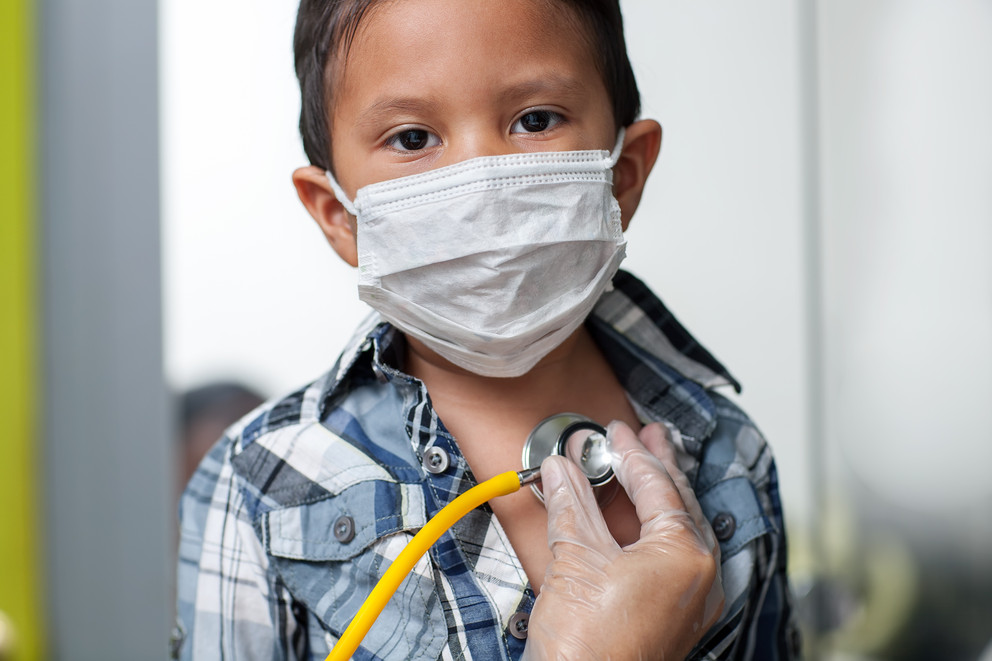 Boy in a mask with a stethascope at doctor's office.