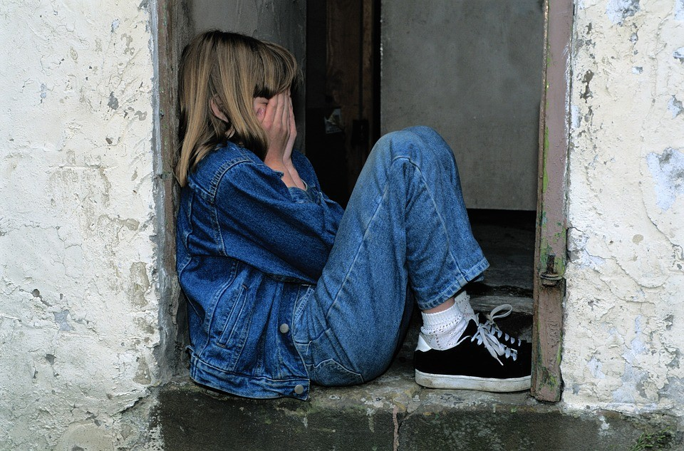 Young girl sitting on the ground crying.