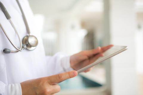 Photo of a doctor looking at a tablet.