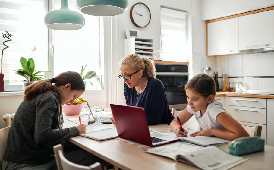 Parents and two children working on laptop computers
