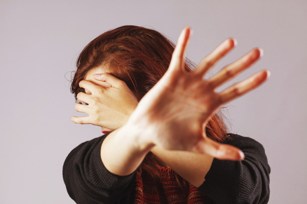 Woman holding up hands to prevent physical abuse.