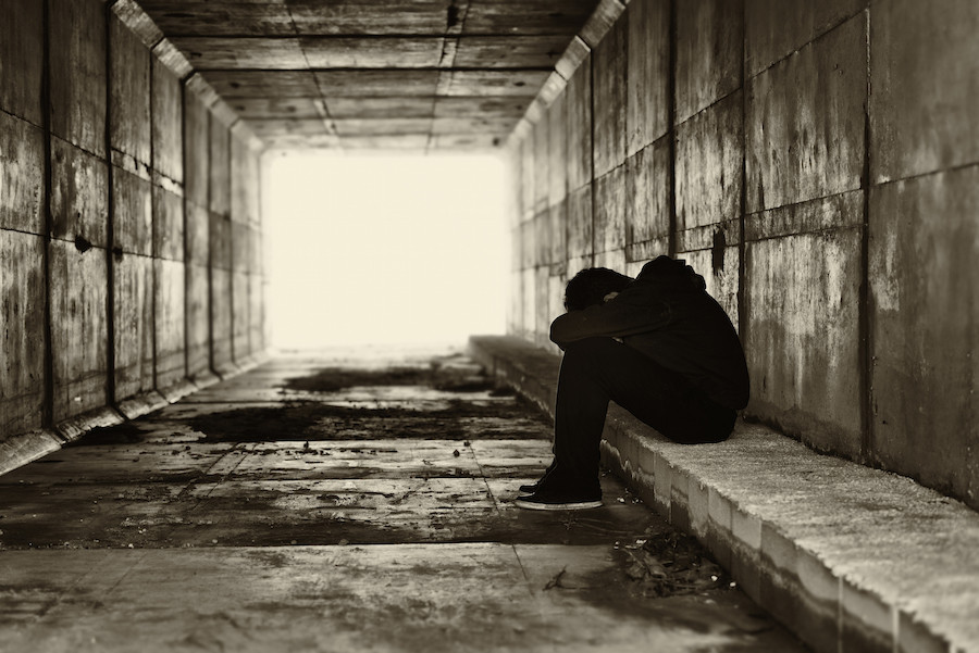 Young adult alone in a tunnel.
