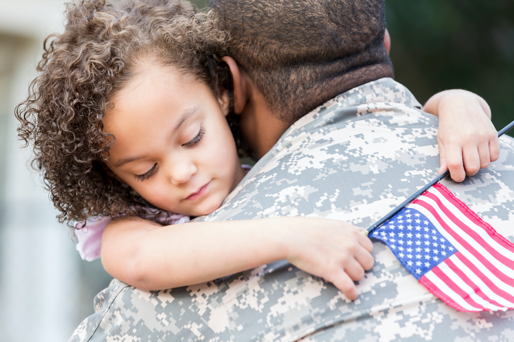 Military dad and small daughter hugging with flag.