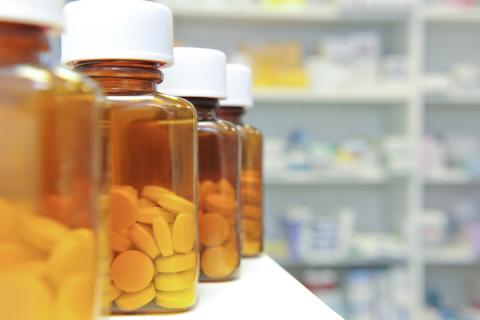 Photo of pill bottles on a counter in a pharmacy.