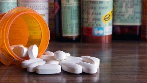 A spilled bottle of prescription pills, with more prescription bottles behind it.