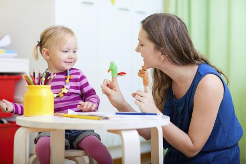 Photo of a woman playing with finger puppets with a toddler.