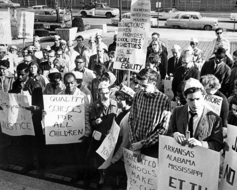 People with picket signs in favor of racial equality and school desegregation.