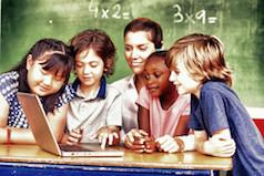 A group of racially diverse children gathered around their teacher.