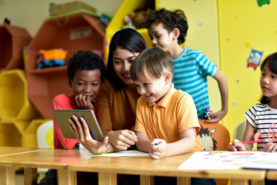 Young children and teacher gathered around an iPad.