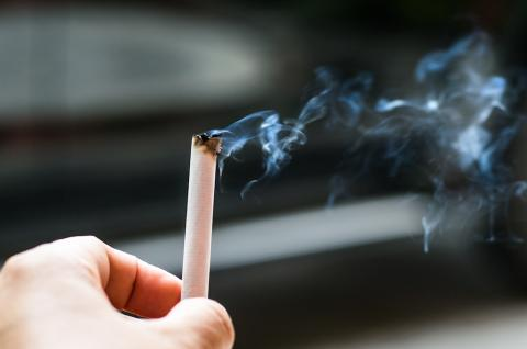 Photo of a hand holding a cigarette that is letting off smoke.