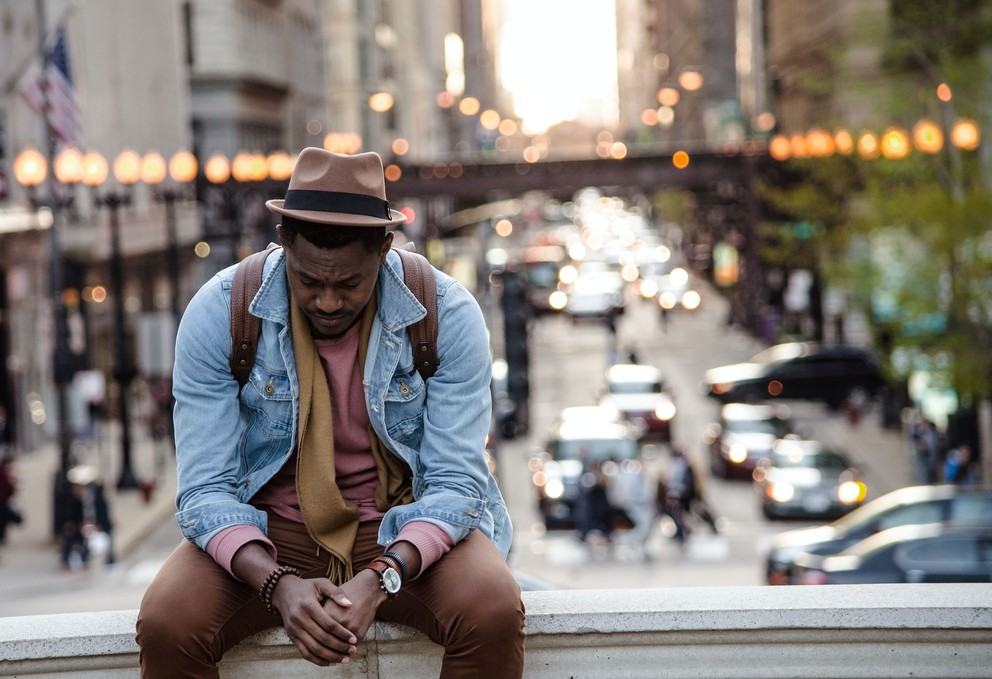 Black man sitting on a bench dealing with grief.