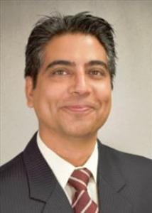 Headshot of Yubraj Acharya with dark hair wearing a suit and red tie.