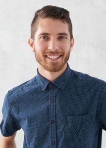 Headshot of Andrew Zeveney, short brown hair, beard, blue collared shirt.