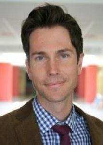 Headshot of Andrew Fenelon with brown hair, a blue and white checkered shirt, red tie, and brown jacket.