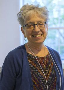 Headshot of Ann Tickameyer in front of window with grey, short hair wearing glasses and blue cardigan.
