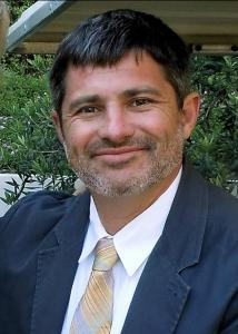 Bachmeier with short dark hair blue jacket and tie