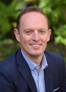 Headshot of Brian King with brown, short hair wearing a blue dress shirt and suit jacket.