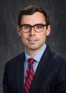 Headshot of Brian Thiede in front of a grey background with dark hair wearing glasses.