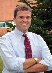 Headshot of Christopher Fowler crossing his arms wearing blue dress shirt and red tie.